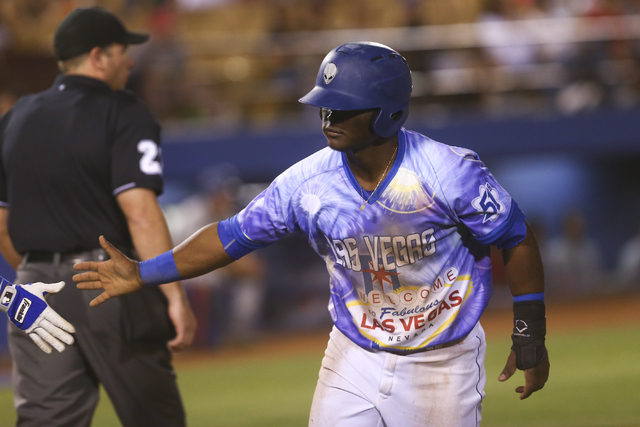Las Vegas 51s player Dilson Herrera high fives a teammate after scoring a run during a baseball game against the El Paso Chihuahuas at Cashman Field in Las Vegas on Friday, May 13, 2016. Chase Ste ...
