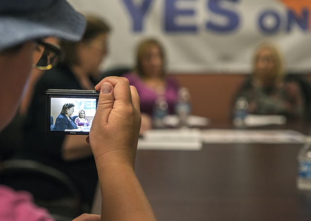 Andrew Davey, left, takes a photo of Lisa Lynn Chapman, left, with Nevada Network Against Domestic Violence, and domestic violence victim Rosa Parra during a press conference for Question 1 on Wed ...