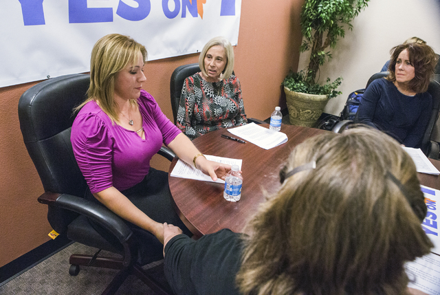 Lisa Lynn Chapman, right, with Nevada Network Against Domestic Violence, holds hands with domestic violence victim Rosa Parra during a news conference Wednesday, Aug. 10, 2016, at Safe House in He ...