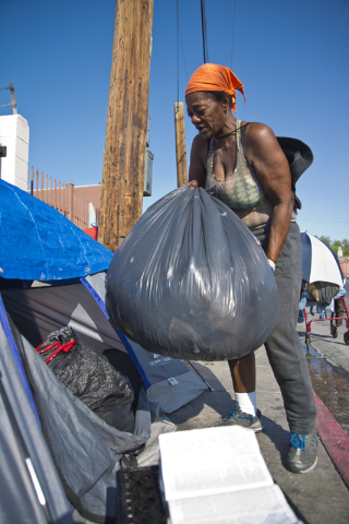 Kathy Washington, who became homeless after her home burned down five weeks ago, packs her things into a makeshift campsite along Foremaster Lane in downtown Las Vegas on Friday, Aug. 5, 2016. Dan ...