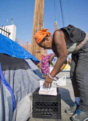 Kathy Washington, who became homeless after her home burned down five weeks ago, reads her Bible at a makeshift campsite along Foremaster Lane in downtown Las Vegas on Friday, Aug. 5, 2016. Daniel ...