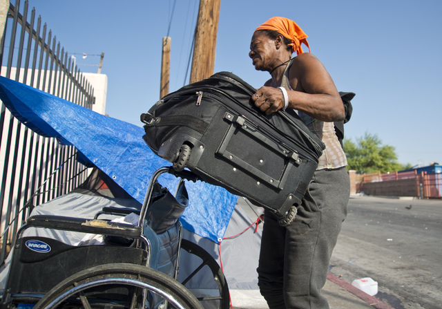 Kathy Washington, who became homeless after her home burned down five weeks ago, packs her things up at a makeshift campsite along Foremaster Lane in downtown Las Vegas on Friday, Aug. 5, 2016. Da ...