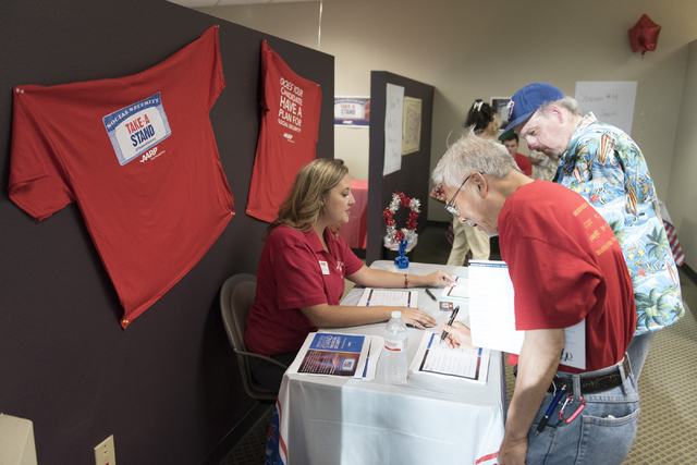 Shannon Nutt, lead organizer with AARP, left, speaks with George Pul, center, and Andrew Rebin, during an open house to discuss protecting Social Security at the AARP Take A Stand campaign office  ...