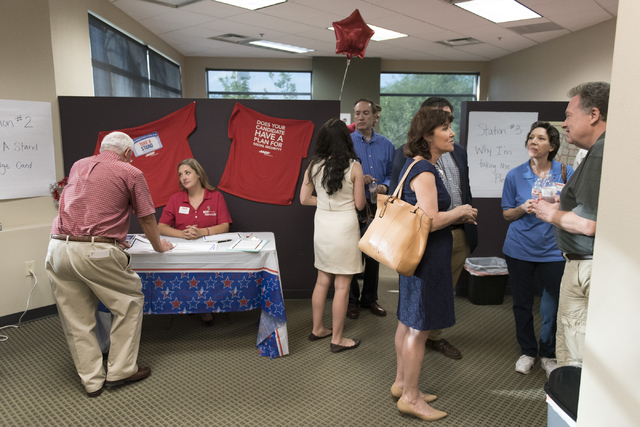 Senior citizens, AARP staff and volunteers and politicians gather during an open house to discuss protecting Social Security at the AARP Take A Stand campaign office in Las Vegas Tuesday, Aug. 2,  ...