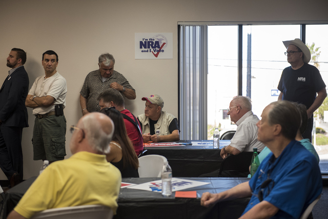 Volunteers and attendees listen to Robert Uithoven, NRA Nevadans for Freedom campaign manager, during the grand opening for a National Rifle Association campaign office at 6375 S. Pecos Road in La ...