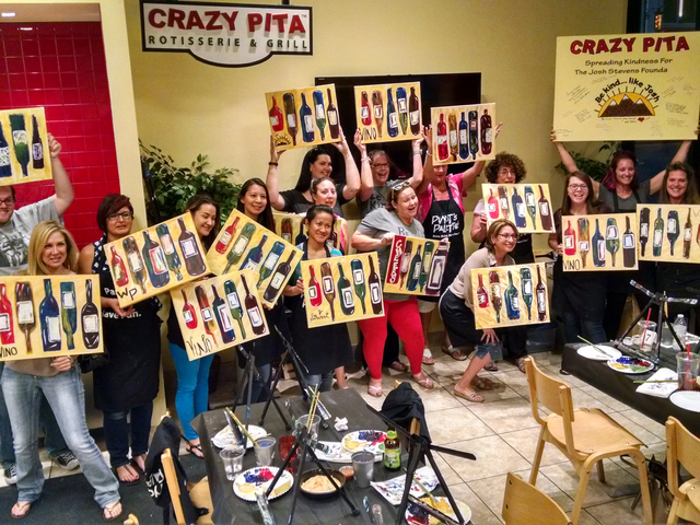 Participants at Paint-Drink-Dine show off their finished paintings July 14. F. Andrew Taylor/View