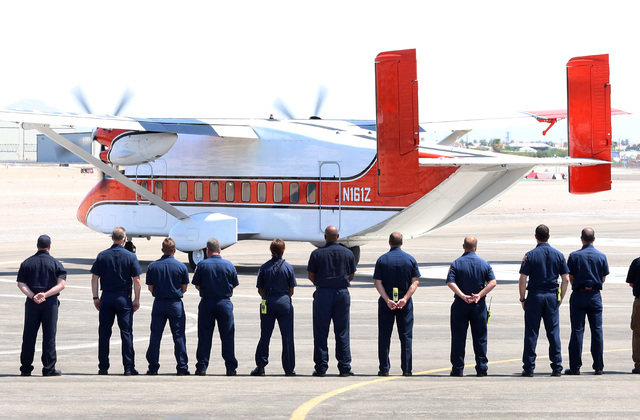 Firefighters from Las Vegas, Nye County, the U.S. Forest Service and Las Vegas police officers line up at the North Las Vegas Airport as the plane carrying the casket of fallen U.S. Forest Service ...