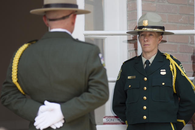 A U.S. Forest Service honor guard member stands outside a Davis Funeral Home for the funeral procession for fallen firefighter Justin Beebe, with the Lolo Hotshot Crew based in Missoula, Montana,  ...