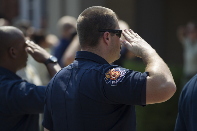 Multi-agency firefighters salute for fallen firefighter Justin Beebe, with the Lolo Hotshot Crew based in Missoula, Montana, during a funeral procession at a Davis Funeral Home on Wednesday, Aug.  ...