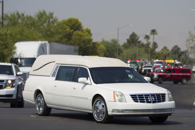 A hearse leads a funeral procession for fallen firefighter Justin Beebe, with the Lolo Hotshot Crew based in Missoula, Montana, at a Davis Funeral Home on Wednesday, Aug. 17, 2016, in Las Vegas. E ...