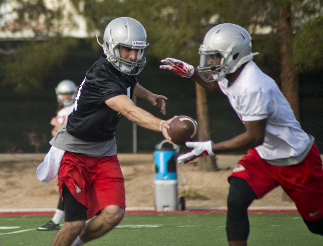 UNLV quarterback Kurt Palandech (14) hands the ball off to running back Lexington Thomas (3) during the first day of spring practice at the Rebel Park practice fields on the UNLV campus in Las Veg ...