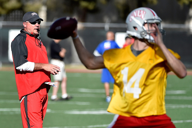 UNLV football head coach Tony Sanchez watches his team run drills, including quarterback Kurt Palandech (14), during the first day of spring practice at Rebel Park at UNLV on Monday, March 16, 201 ...