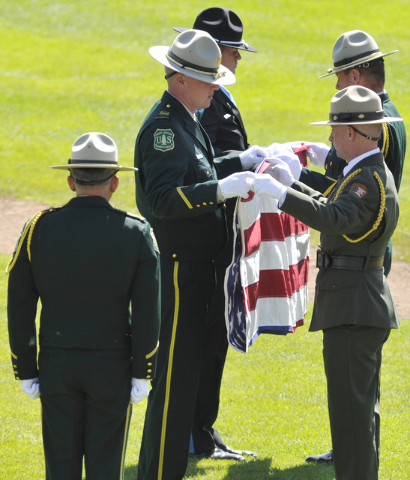 Members of the honor guard fold an American flag during a memorial service for fallen U.S. Forest Service firefighter Justin Beebe, Saturday, Aug. 20, 2016, in Missoula, Mont. (Tommy Martino/The M ...