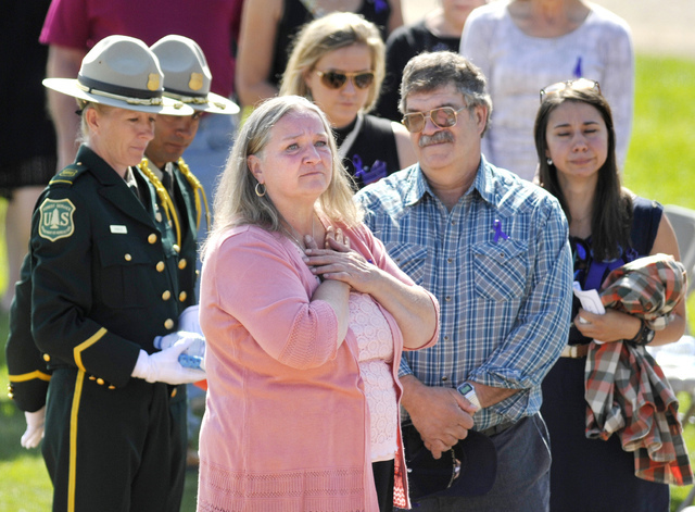 Fallen U.S. Forest Service firefighter Justin Beebe's parents Betsy, front, and Sheldon Beebe look out over the crowd before memorial service for Justin Beebe, Saturday, Aug. 20, 2016, in Missoula ...