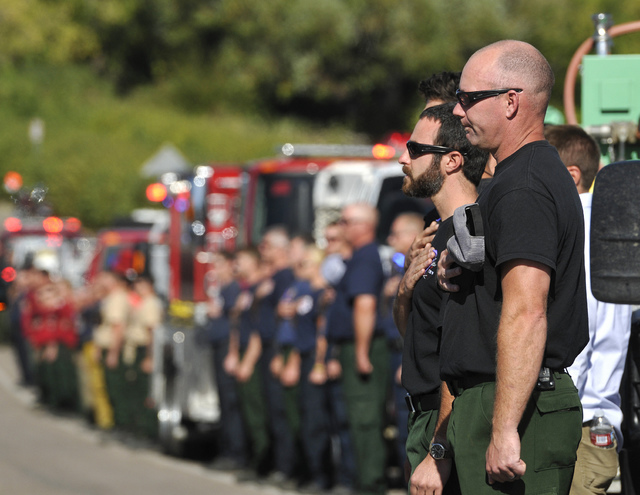 Firefighters stand at attention as fallen U.S. Forest Service firefighter Justin Beebe's family passes during a procession for Beebe, Saturday, Aug. 20, 2016, in Missoula, Mont. (Tommy Martino/The ...