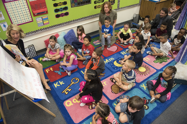 Kindergarten teacher Jordan Pirrone, left, reads to kindergarten students on the first day of school at James B. McMillan Elementary School in Las Vegas on Monday, Aug. 29, 2016. Clark County Scho ...