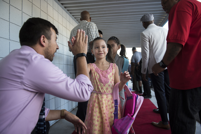 Founder of Nevada Youth Network Michael Flores, left, greets students on the first day of school at Matt Kelly Elementary School in Las Vegas on Monday, Aug. 29, 2016. Flores recruited over 100 ma ...