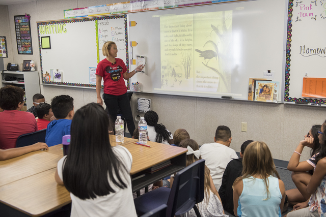 Fifth grade teacher Nicole Gladish, left center, reads a book through a projector to her students during the first day of school at William V. Wright Elementary School in Las Vegas on Monday, Aug. ...