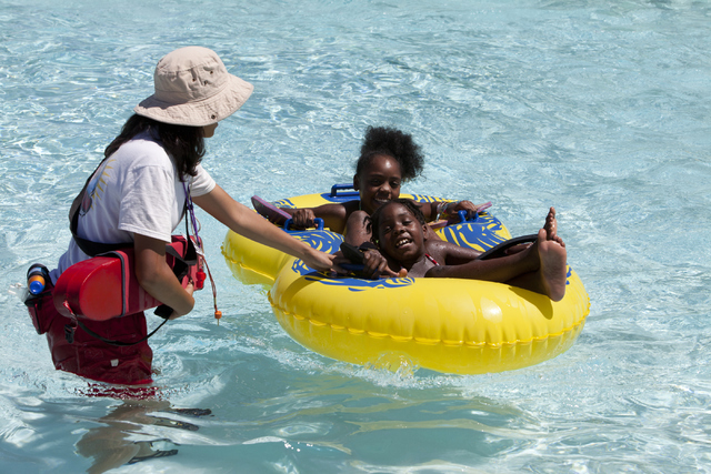 Cowabunga Bay Las Vegas employee pulls in siblings Ahmyah and Ahkijah's raft after they went down the Point Panic ride at the Cowabunga Bay Las Vegas water park in Henderson on Wednesday, June 13, ...