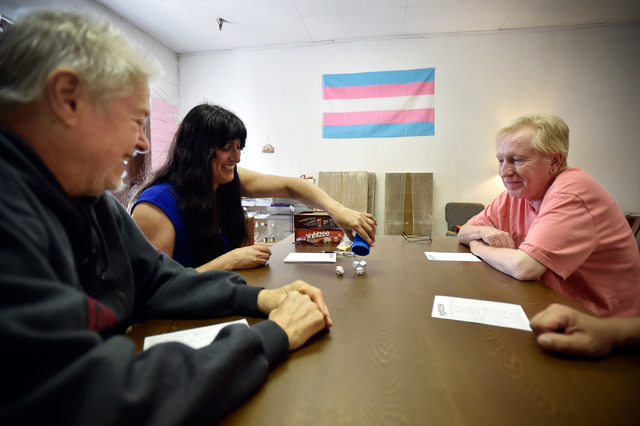 Volunteer Marty Brown, left, founder Jamie Sprague-Ballou and Steve Anderson play a game of Yahtzee at Transcending the Gender Box Monday, Aug. 1, 2016, in Las Vegas. The center offers the transge ...