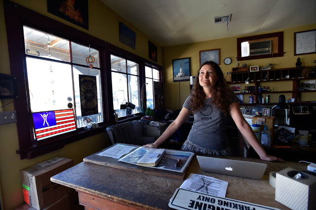 Cameron Hall answers questions for visitors in the Burning Man office in Gerlach, Nev., Tuesday, Aug. 23, 2016. After attending the Burning Man festival, Hall relocated to the small northern Nevad ...