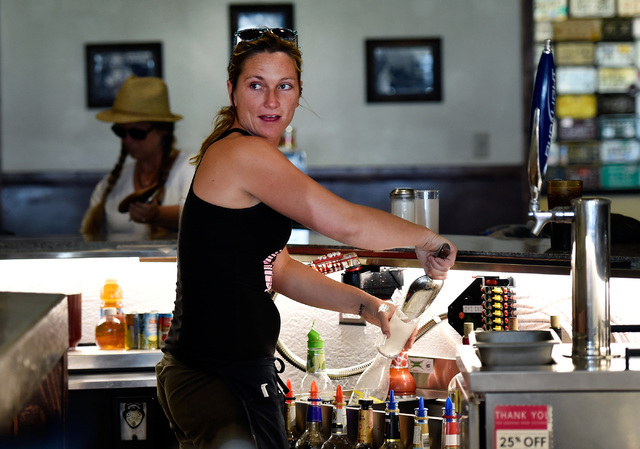 Lacey Holle tends bar at Bruno's Country Club, Tuesday, Aug. 23, 2016, in Gerlach, Nev. The residents of the small northern Nevada town have mixed feelings about the annual counterculture event th ...