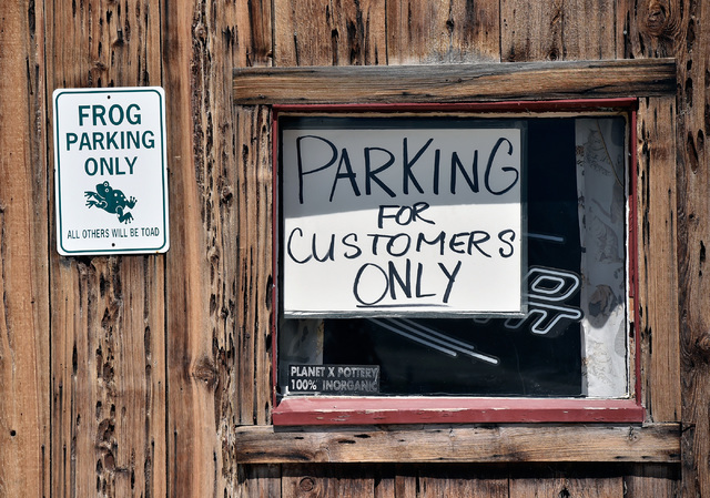 """Signs are seen posted in the window of a local business to discourage """"burners"""" from taking up parking spaces, Tuesday, Aug. 23, 2016, in Gerlach, Nev. The residents of the small ..."""