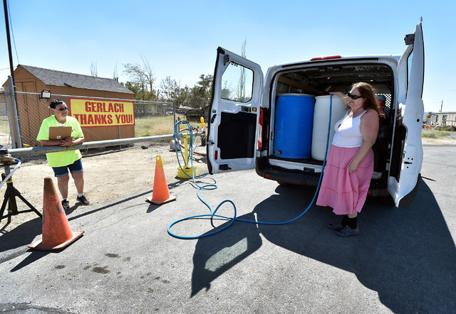 A women who gave her name as the Kitchen Wench, right, fills barrels with water sold by water department volunteer Cindy Carter in Gerlach, Nev., Tuesday, Aug. 23, 2016. The town began selling wat ...