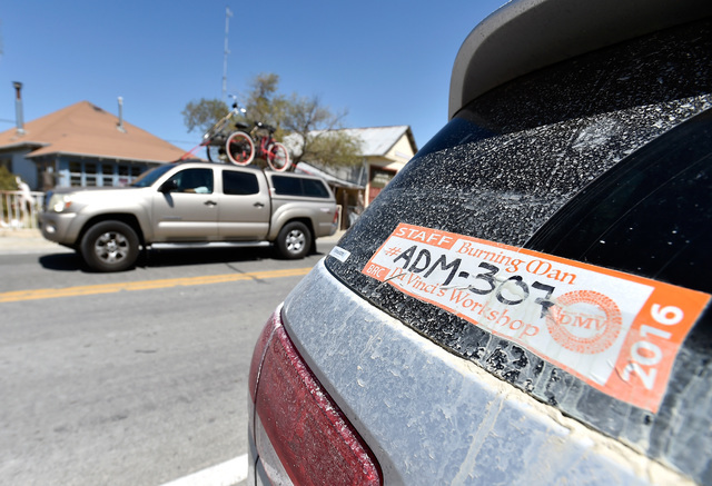 A Burning Man parking sticker is seen pasted on a vehicle along highway 447 in Gerlach, Nev. Tuesday, Aug. 23, 2016.  The residents of the small northern Nevada town have mixed feelings about the  ...