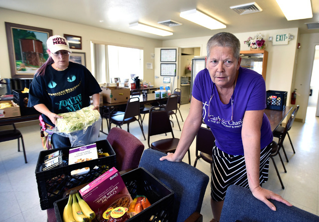 Schatzi Gambrell, right, speaks about the Burning Man festival while loading crates with food with her assistant Melissa Edgecomb at the senior citizen center in Gerlach, Nev. Tuesday, Aug. 23, 20 ...