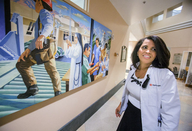 Sister Xiomara Mendez-Hernandez stands in front of a wall mural depicting the history of the St. Rose Dominican hospitals on Wednesday, Aug. 17, 2016, at St. Rose Dominican Hospital, Siena campus. ...