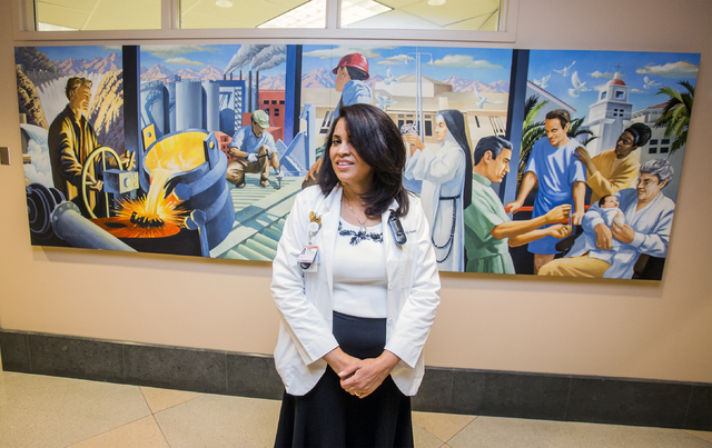 Sister Xiomara Mendez-Hernandez stands in front of a wall mural depicting the history of the St. Rose Dominican Hospital, Siena campus, on Wednesday, Aug. 17, 2016, at St. Rose Dominican Hospital  ...