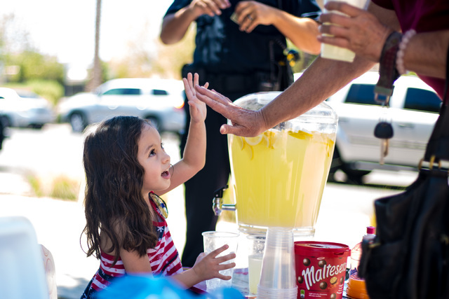 Theresa Ann Babcock, 3, gets a high-five at her lemonade stand outside of Henderson City Hall July 19. Elizabeth Brumley/View