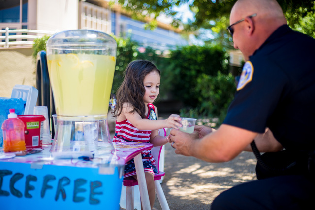 Henderson resident Theresa Ann Babcock, 3, gives a glass of lemonade to Henderson Police Officer Michael Condratovich at her lemonade stand outside of Henderson City Hall July 19. She wanted to sh ...