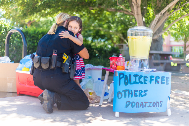 Henderson Police Officer June Castro receives a hug from Theresa Ann Babcock, 3, at her lemonade stand outside of Henderson City Hall July 19. Elizabeth Brumley/View
