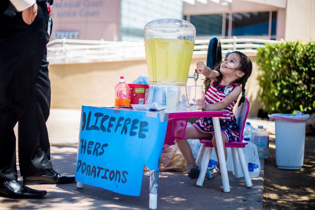 Theresa Ann Babcock, 3, pours a glass of lemonade at her lemonade stand outside of Henderson City Hall July 19. Elizabeth Brumley/View