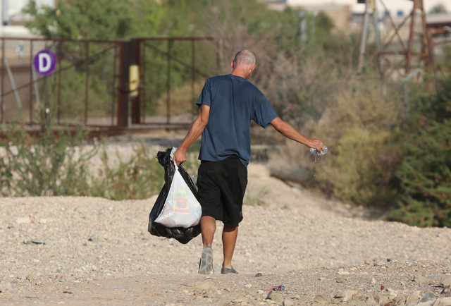 Colton, a homeless Marine veteran who declined to give his last name, carries his food that was provided by HELP of Southern Nevada and the VA's homeless vets outreach team on Thursday, July 28, 2 ...