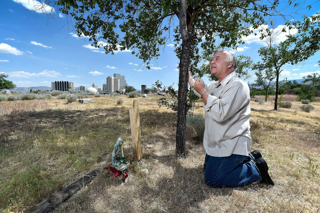 """Joseph Galata kneels before a child's grave marker in a historic cemetery Tuesday, June 7, 2016, in Reno.  """"It's for the kids,"""" he said, wanting to save the cemetery from developers. (David Becker ..."""