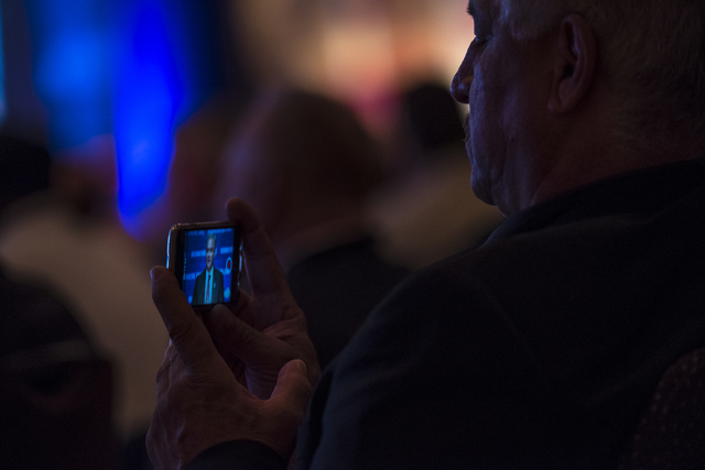 A man records a video on his phone as Democratic vice presidential nominee Tim Kaine speaks during the Iron Workers International 43rd Convention at The Mirage hotel-casino in Las Vegas on Monday, ...