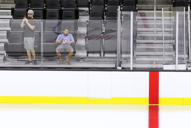 Joe Hulbert, left, takes video of the ice and Rich Belsky looks at a pamphlet near center ice during an open house for prospective 2017 Vegas NHL hockey season ticket holders at T-Mobile Arena Mon ...