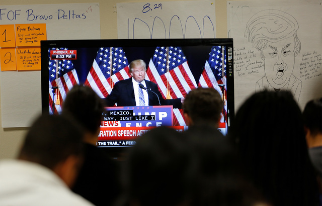 People from Nevada progressive organizations watch Republican presidential candidate Donald Trump speaking in Phoenix on a screen at an office of For Nevada's Future in North Las Vegas, Wednesday, ...
