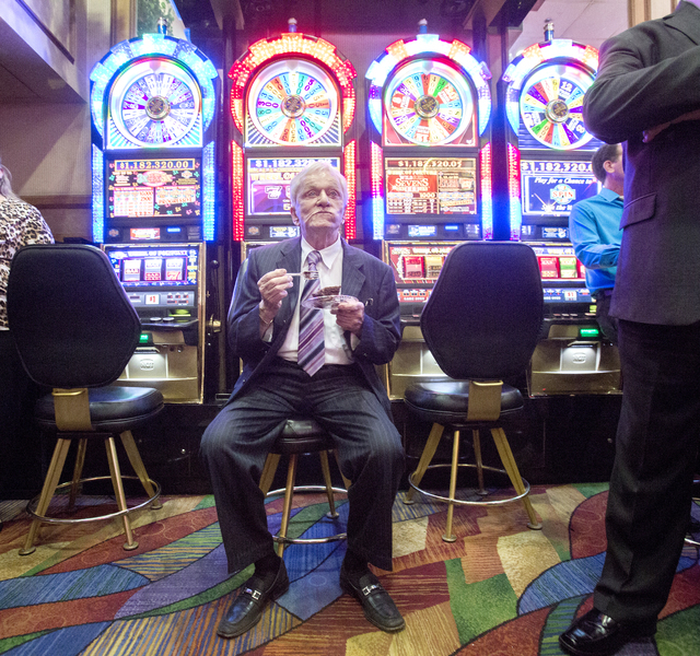 Don Laughlin, owner of the Riverside Resort, eats a piece of chocolate cake near a bank of slot machines during the 50th anniversary party for the resort in Laughlin on Tuesday, Aug. 2, 2016. (Jef ...