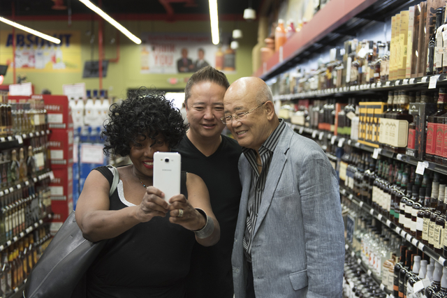 Rheata Porte, left, takes a selfie with Hae Un Lee, founder of Lee's Discount Liquor, right, and his son, Kenny Lee, president of the company, during the grand opening of the store at 1450 W. Hori ...
