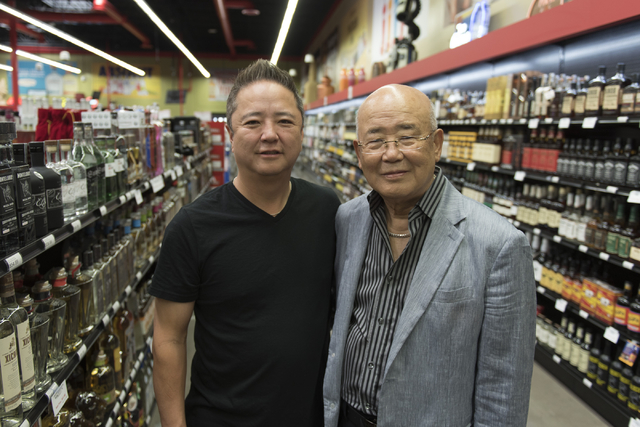 Hae Un Lee, founder of Lee's Discount Liquor, right, and his son, Kenny Lee, president of the company, stand in an aisle during the grand opening of the store at 1450 W. Horizon Ridge Parkway in H ...