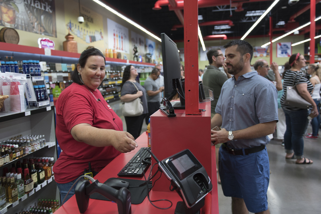 Sherry Strickland, left, helps customer, Ron Principio, at the register during the grand opening of the Lee's Discount Liquor store at 1450 W. Horizon Ridge Parkway in Henderson on Saturday, Aug.  ...