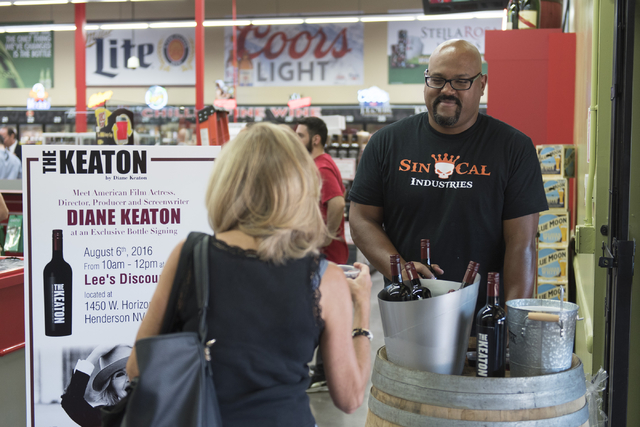 M.J. Taboado, right, hands out samples of Diane Keaton's wine during the grand opening of Lee's Discount Liquor at 1450 W. Horizon Ridge Parkway in Henderson on Saturday, Aug. 6, 2016.(Jason Oguln ...
