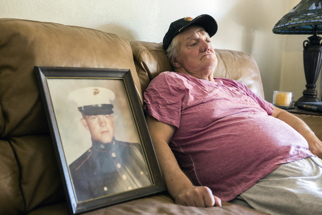 Marine veteran Stanley Furrow sits in the family's home in Las Vegas, Thursday, Aug. 11, 2016. On the left is a photo of him while he as stationed at Marine Corps Base Camp Lejeune, N.C. (Jeff Sch ...
