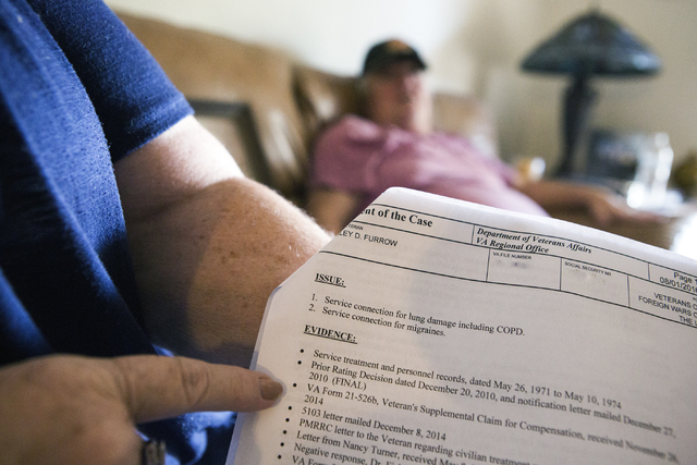 Linda Furrow, points to evidence on a Veterans Affairs form showing the family health issues while her husband, Marine veteran Stanley Furrow, sits in the family's home in Las Vegas on Thursday, A ...