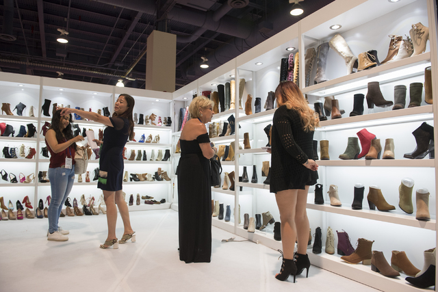 Attendees look at shoes in the M&L Beverly Hills booth during the MAGIC trade show at the Las Vegas Convention Center on Monday, Aug. 15, 2016. Martin S. Fuentes/Las Vegas Review-Journal