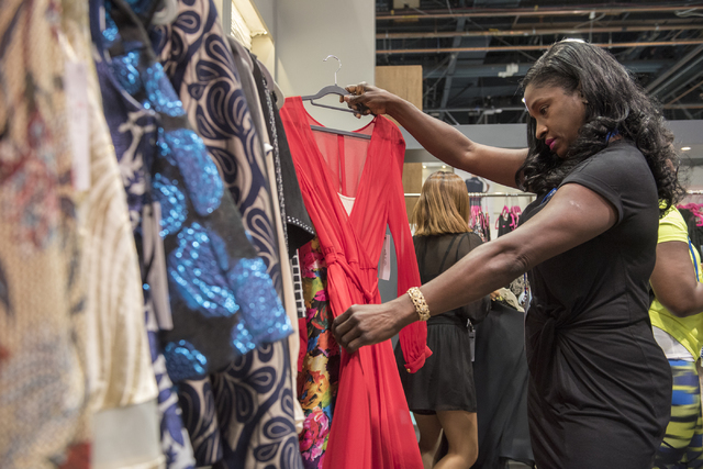 Buyer Deborah O'Neal from British Virgin Islands looks through clothing at the booth of Ark & Co. during the MAGIC trade show inside the Las Vegas Convention Center on Monday, Aug. 15, 2016. M ...